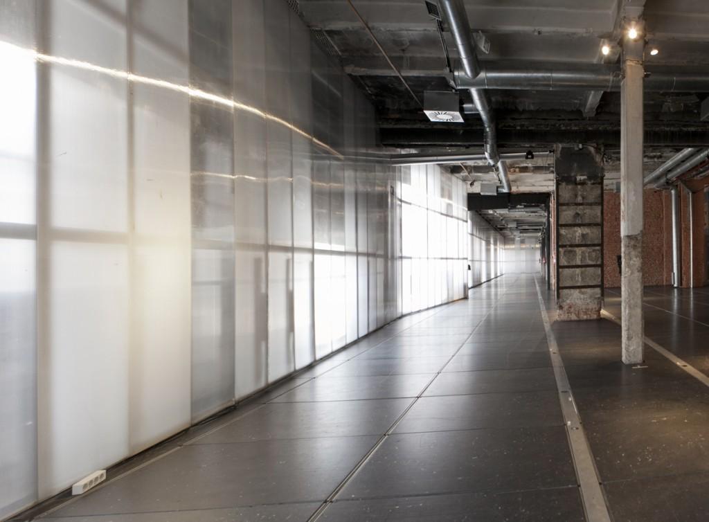 Sala del espacio Gran Nave Industrial para alquilar en Madrid con luz natural por la pared translúcida que puede oscurecerse gracias a un sistema eléctrico de stores administrable.